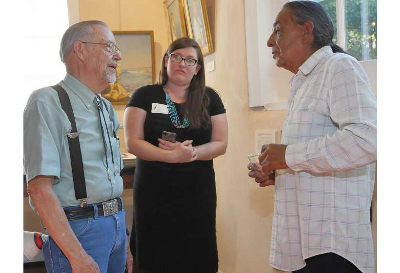 Texas patron Phil Woodard, University of Oklahoma intern Chelsea Herr, and Taos Pueblo resident Fred Lujan, Jr. discuss the Sharp exhibition.